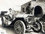 Frank Chapman Jr. [?] in a touring car, beside the Palmetto Grove house, Covina, California, 1909
